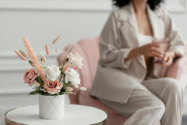 白い花瓶に白とピンクの花の花束、背景にスーツを着た女性