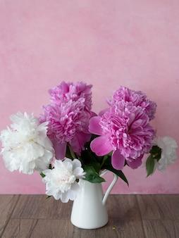 Букет из белых и розовых пионов в белом кувшине на розовом фоне. крупный план, выборочный фокус.
