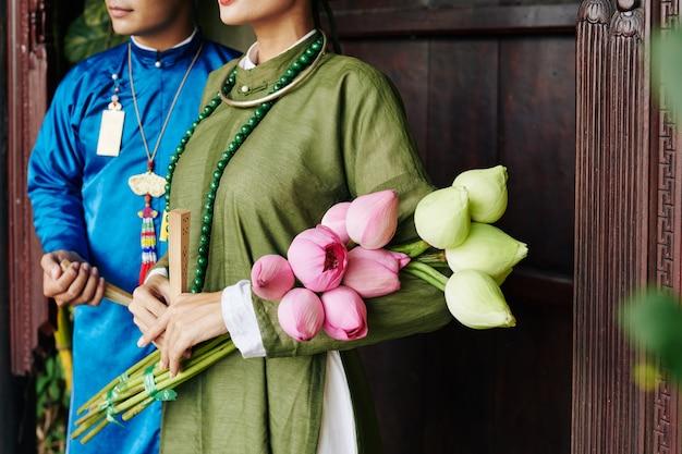 그녀의 신랑 옆에 서 있는 신부의 손에 흰색과 노란색 연꽃 꽃다발