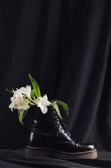 어두운 부팅에서 녹색 잎과 하얀 꽃의 꽃다발