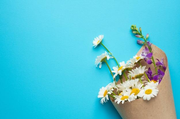 紙に白いデイジーの花と紫のデルフィニウムの花束