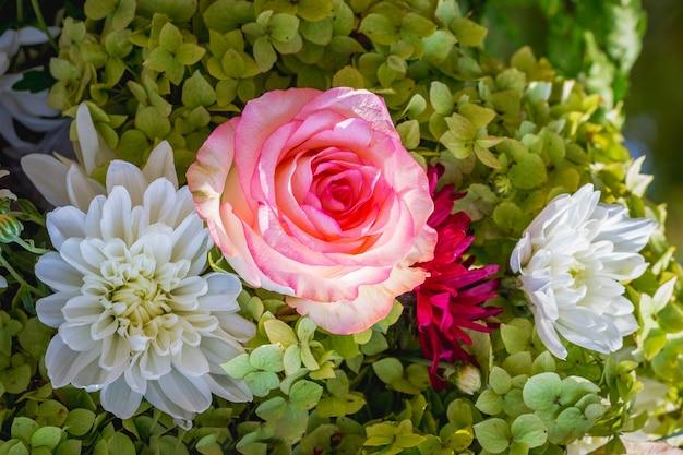 中央に白い花とピンクのバラの花束_