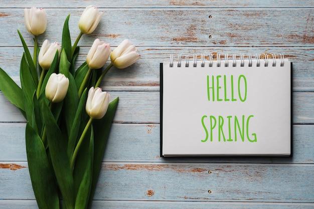 こんにちは春をレタリングとノートブックで青いボードの背景にチューリップの白い花の花束