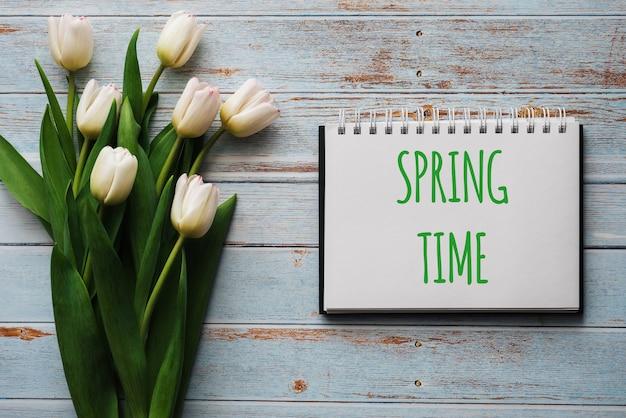 春の時間をレタリングとノートブックで青いボードの背景にチューリップの白い花の花束