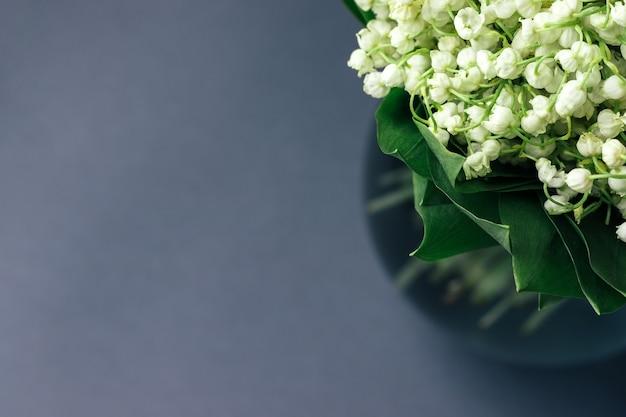 녹색 계곡의 흰 백합 꽃다발 복사 공간이 부드러운 회색 배경에 유리 꽃병에 나뭇잎. 선택적 초점. 근접 촬영보기