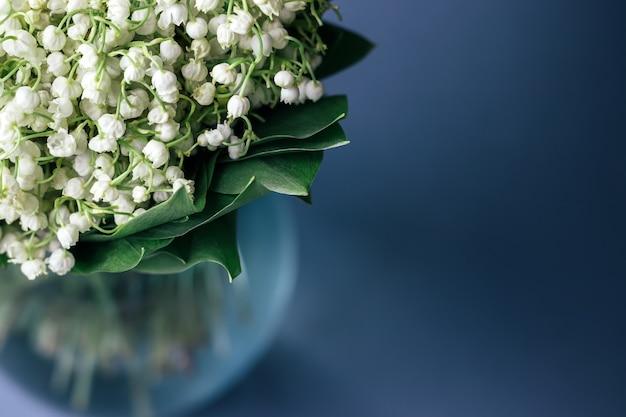 Букет из белых ландышей в зеленых листьях в стеклянной вазе на мягком сером фоне с копией пространства. выборочный фокус. крупным планом вид.