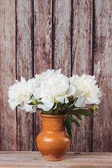Букет белых пионов в глиняном кувшине на деревенском деревянном столе свежие садовые цветы