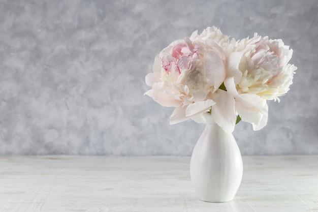 木製のテーブルの上に花瓶に白い牡丹の花束。ギフトバレンタインデー。