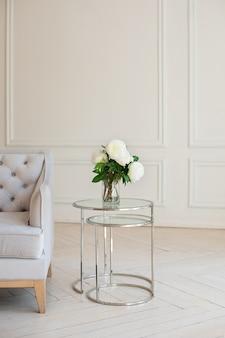 白い牡丹の花束は、白いリビングルームの灰色のソファーの近くのテーブルの上の花瓶に立っています。