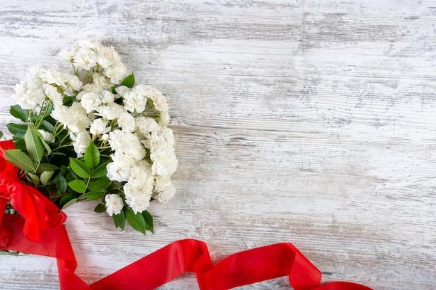 赤いリボンと白いバラの花束