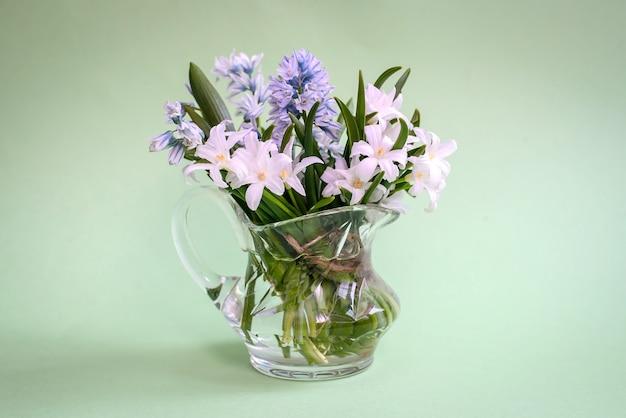 Букет белых весенних цветов в маленькой стеклянной вазе