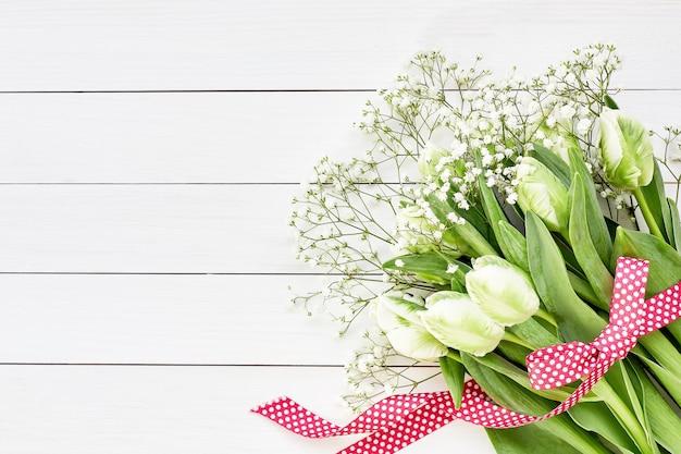 白い木製の背景に赤いリボンで飾られた白いチューリップとカスミソウの花束。上