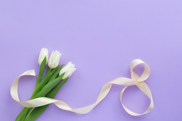 Букет из белых тюльпанов и восьмерки из атласной ленты на фиолетовой сирени.