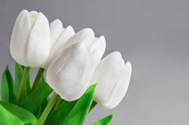 Букет из белых тюльпанов на сером фоне, подарок женщине, концепция женского праздника