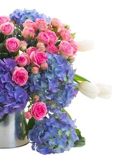 白いチューリップ、ピンクのバラ、青いオルテンシアの花の花束が白いスペースに孤立してクローズアップ