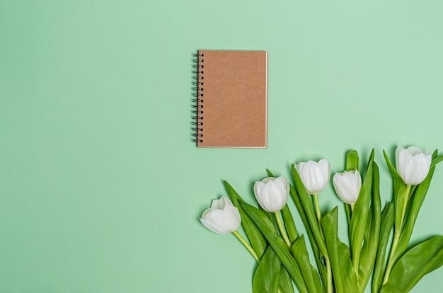 녹색 배경에 노트에 대 한 노트북으로 흰색 튤립 꽃다발. 봄 개념, 복사 공간, 평평하다, 텍스트에 대 한 장소. 배너. 위에서 봅니다.