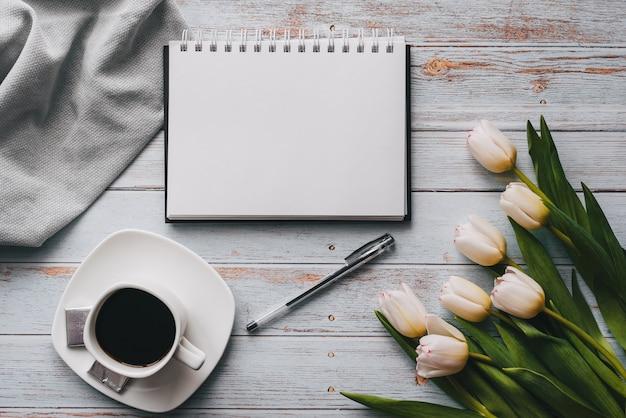 空のノートブック、木製の背景にコーヒーカップと白いチューリップの花束
