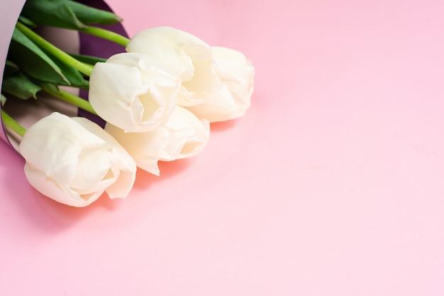 ピンクの紙に白いチューリップのラッパーのブーケ。最小限の自然フラット横たわっていた。母の日と3月8日のグリーティングカード。春休みのやさしいコンセプト