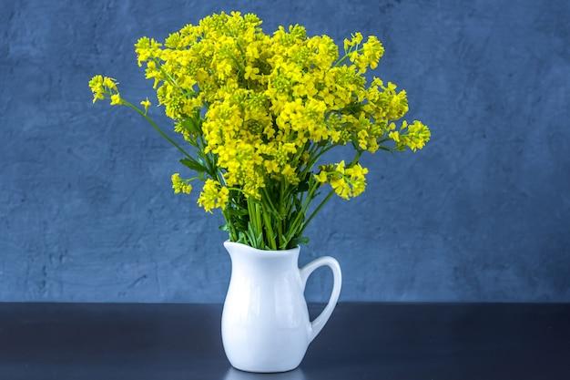 暗い青色の背景の上に花瓶に野生の花の花束。新鮮な春の花。