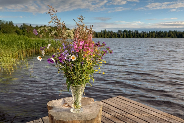 숲의 호수에 크리스탈 꽃병에 야생 꽃의 꽃다발.