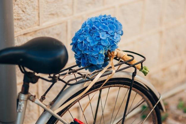 Букет полевых цветов на багажнике велосипеда. летние прогулки по полю на велосипеде.