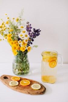 Букет полевых живых цветов в вазе и домашний лимонад с апельсинами и лимонами