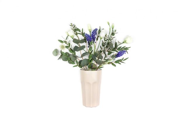ベージュのガラスのワイルドフラワーの花束。トップビュー、フラットレイアウト