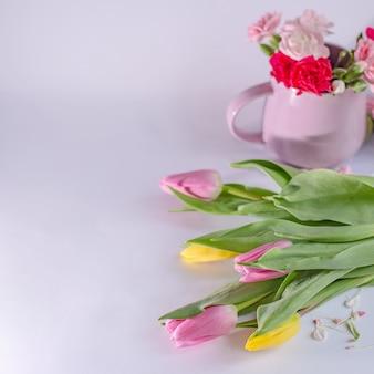 Букет из желтых и розовых тюльпанов на белом фоне. чашка с цветами. день святого валентина и фон дня матери.