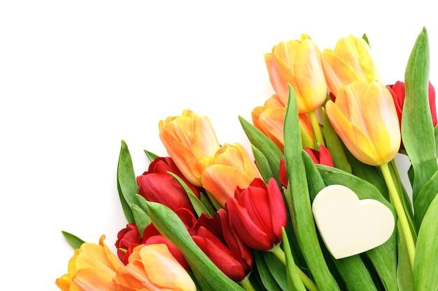 Букет из желтых и красных тюльпанов с маленьким сердечком на белом фоне. весной и летом фон. день матери, пасха и сезонный праздник