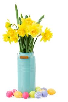 Букет из желтых нарциссов в синей вазе с пасхальными яйцами на белом