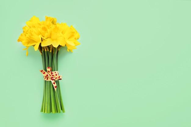 Букет из желтых нарциссов, украшенный лентой с сердечками на зеленой стене. плоская планировка, копирование пространства для текста