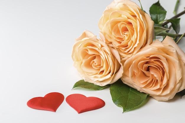 白い背景の上の黄色いバラと2つのハートの花束。コピースペース付きのバレンタインデーのグリーティングカード。