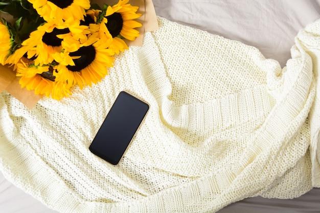 패브릭 흰색 격자 무늬 배경에 전화와 노란 해바라기 꽃다발