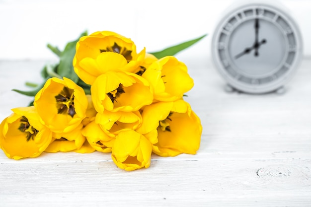 黄色いチューリップの花束とレトロな時計