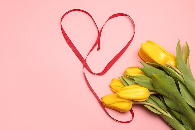 コピースペースとピンクの背景に赤いリボンで作られた黄色いチューリップとハートの花束。母の日またはバレンタインデーのギフトコンセプト。クローズアップ写真