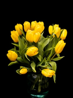 黒の背景にガラスの花瓶に黄色いチューリップの花束。美しい花。庭の植物。バレンタイン・デー。高品質の写真