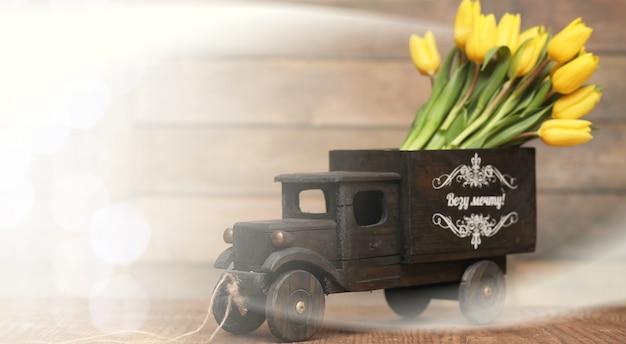 Букет желтых тюльпанов в вазе на полу
