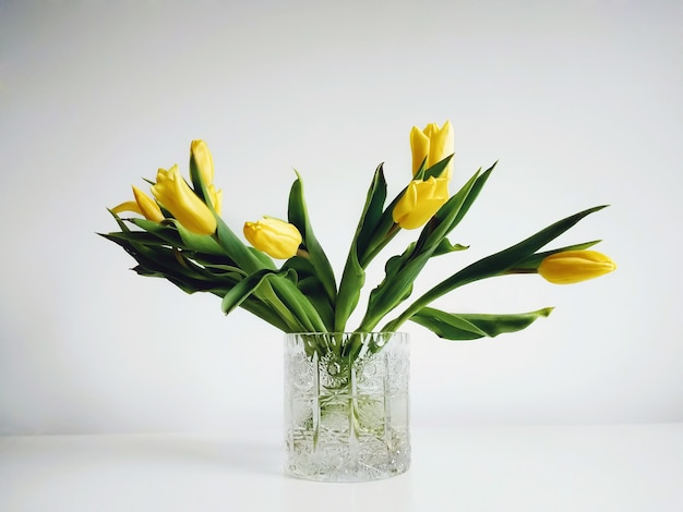 Букет желтых тюльпанов в вазе под огнями на белом фоне.