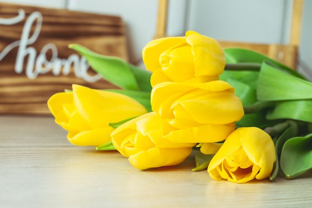 Букет из желтых тюльпанов на деревянной поверхности.
