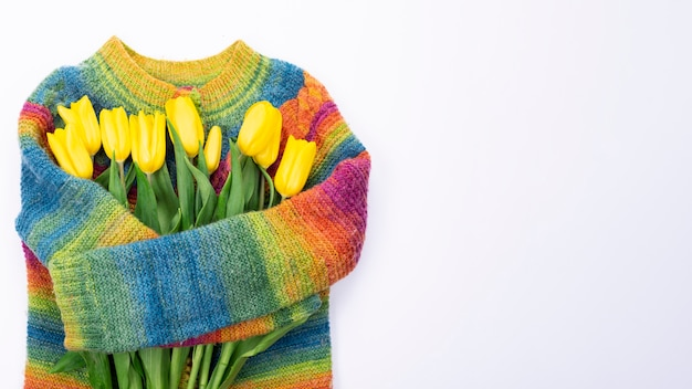 色とりどりのニットセーターの背景に黄色いチューリップの花束、上面図、女性の日の黄色いチューリップの花束、春の花のコンセプト