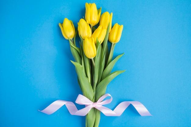 青い背景の上の黄色いチューリップの花束