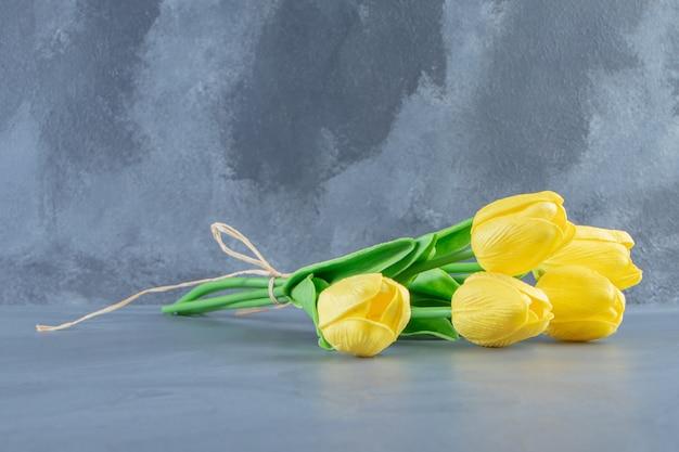 白いテーブルの上の黄色いチューリップの花束。