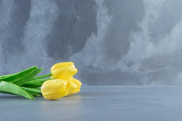 흰색 테이블에 노란색 튤립 꽃다발.