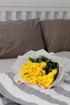Букет из желтых тюльпанов с конфетти красных сердечек в постели в спальне. концепция праздника, дня рождения, женского дня. сюрприз в постели. доброе утро. натюрморт