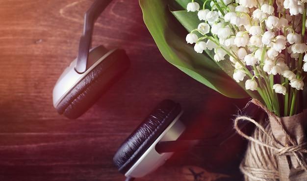 木製のテーブルの上の谷の若いユリの花束