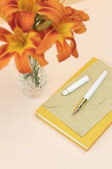 Bouquet orange lilies in vase with yellow notebook and envelope