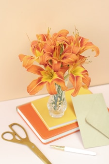 bouquet orange lilies with gold scissors and craft envelope