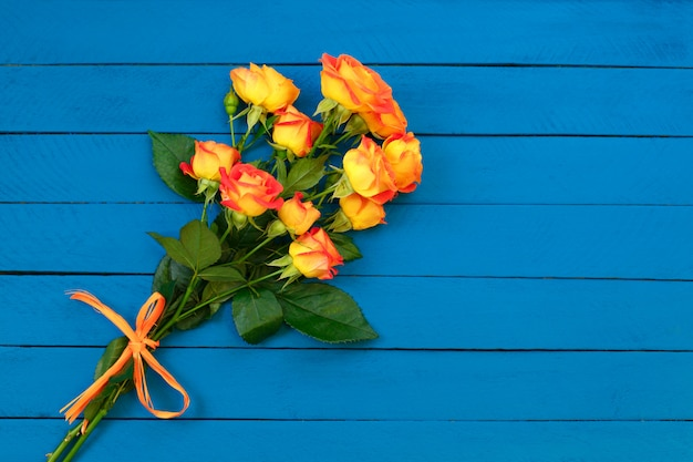 Bouquet of  orange roses on blue wooden