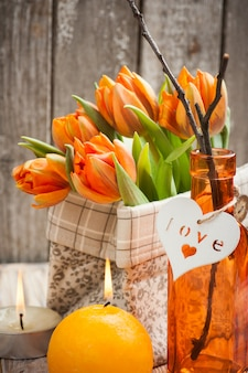 Bouquet of orange tulips, lit candles