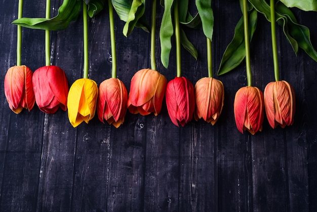 Bouquet of orange and yellow tulips over a rustic wood table top
